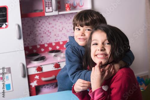 Leinwandbild Motiv Two siblings having great hug and playing at toy kitchen