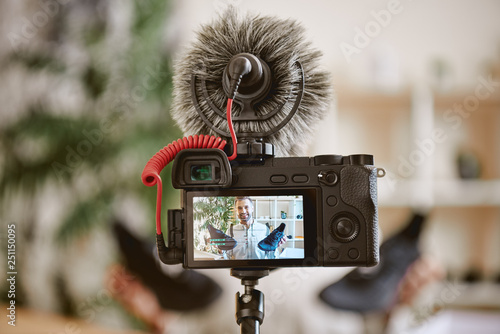 In focus. Close up photo of camera display with cheerful male blogger holding black sneakers while recording new video