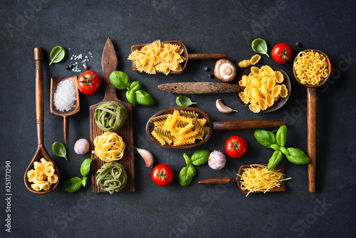 Leinwanddruck Bild Various pasta on wooden spoons over stone background