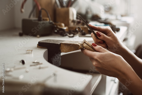 Master's hands. Side view of a female jeweler hands creating a silver ring at her workbench. Making accessories © dima_sidelnikov