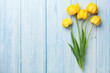 Yellow tulips on wooden table - 251179801