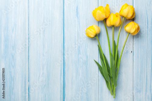 Leinwandbild Motiv Yellow tulips on wooden table