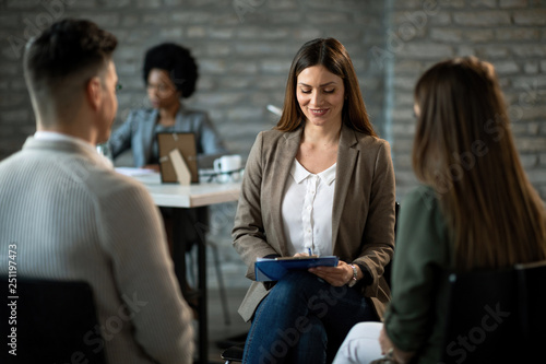 Happy financial advisor having an interview with a couple in the office.