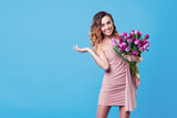 Young happy smiling redhead woman holding bouquet of colorful spring flowers isolated on blue background. Pink tulips, festive bouquet in honor of women's day on March 8 or birthday