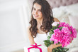 Very beautiful woman with peony and gift box indoors