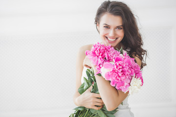 Close up portrait of young beautiful woman with flowers indoors