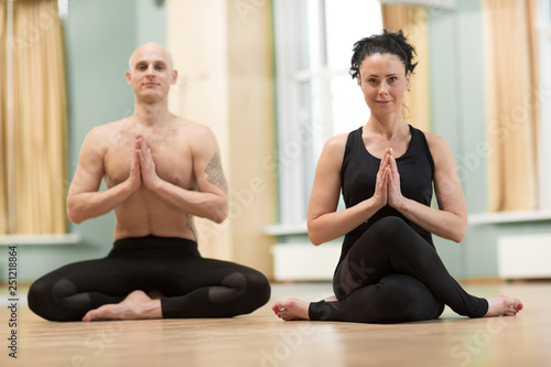 Horizontal shot of a mature couple enjoying practicing yoga together. Beautiful woman and shirtless athletic man meditating together at the gym. Happiness, meditation, love, sports concept
