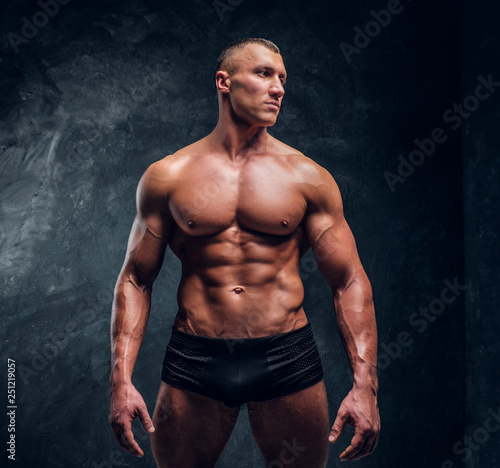 Leinwandbild Motiv A handsome athletic man with perfect pumped body wearing underwear. Studio photo with dark wall background