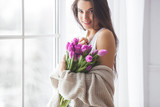 Fototapeta Tulipany - Attractive young woman with flowers indoors in the bedroom. Portrait of beautiful lady at home. Close up shot of female with tulips. © olenachukhil