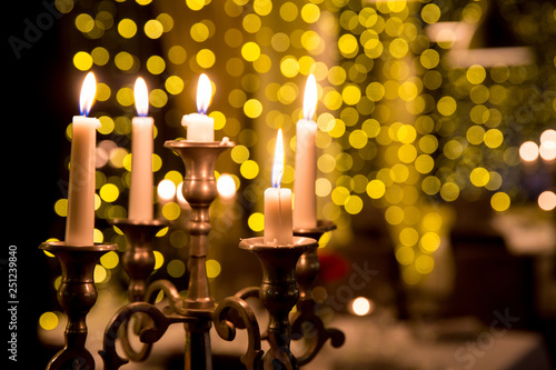 Candles to a beautiful candlestick.  Candles lighting in the dark night with bulbs lights in blur © fotosr52
