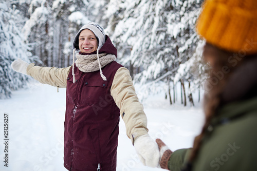 Leinwandbild Motiv Waist up portrait of happy young couple enjoying walk in winter forest, focus on man leading girlfriend by hand, copy space