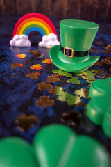 Saint Patrick's Day green leprechaun hat on gold shamrocks reflecting colorful rainbow