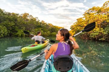Couple kayaking together in mangrove river of the Keys, Florida, USA. Tourists kayakers touring the river of Islamorada.