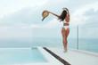 Leinwandbild Motiv Summer. Happy woman in swimsuit near swimming pool with sea view