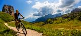 Turystyczne kolarstwo w Cortina d'Ampezzo, wspaniałe Cinque Torri i Tofana w tle. Man riding MTB enduro flow trail. Prowincja Południowego Tyrolu we Włoszech, Dolomity.