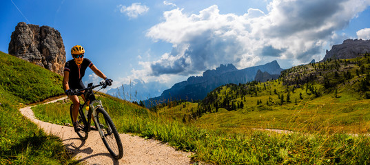 Tourist cycling in Cortina d'Ampezzo, stunning Cinque Torri and Tofana in background. Man riding MTB enduro flow trail. South Tyrol province of Italy, Dolomites. © Gorilla