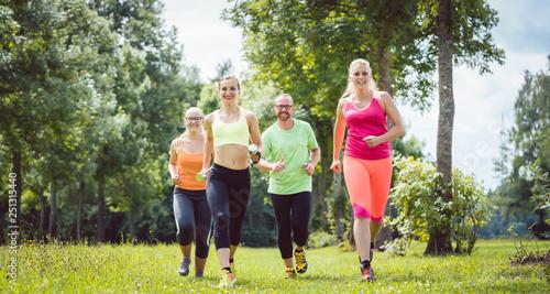 Leinwandbild Motiv Family with personal Fitness Trainer jogging