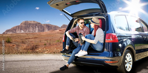 obraz lub plakat Summer car trip on USA road. Two young people and big blue car with suitcase. Free space for your decoration.