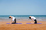 Women practicing camel yoga pose on the beach