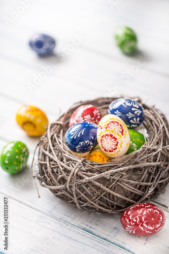 Close-up multicolored easter eggs in basket on wooden table © weyo