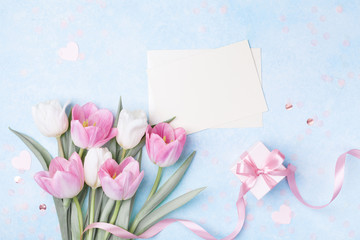 Women Day, Mother day background with envelope, gift box and beautiful spring tulip flowers on pastel blue desk. Flat lay. © juliasudnitskaya