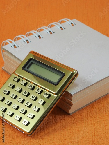 Close-up of a golden calculator and a small blank notepad on an orange surface. The focus is on the calculator. The notepad is closed. - 251339022