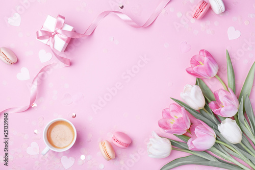 Morning cup of coffee, cake macaron, gift or present box and spring tulip flowers on pink background. Beautiful breakfast for Women day, Mother day. Flat lay. © juliasudnitskaya