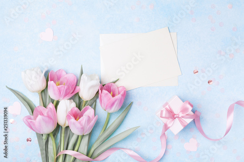 Women Day, Mother day background with envelope, gift box and beautiful spring tulip flowers on pastel blue desk. Flat lay.