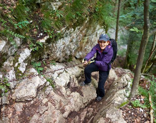 Woman climbing a difficult trail