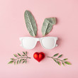 Happy Easter minimal concept. Bunny rabbit face made of natural green leaves with sunglasses and red heart on pastel pink background. Flat lay.