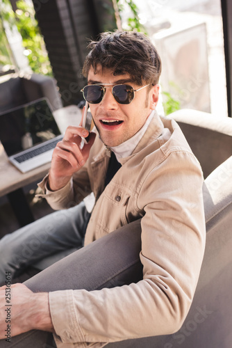 selective focus of man in sunglasses talking on smartphone near laptop in cafe
