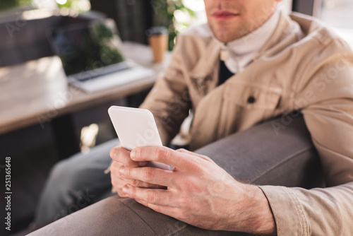 cropped view of trendy man sitting near laptop and paper cup and using smartphone