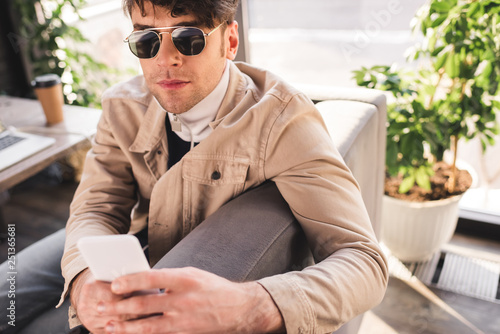 selective focus of trendy man in sunglasses using smartphone in cafe