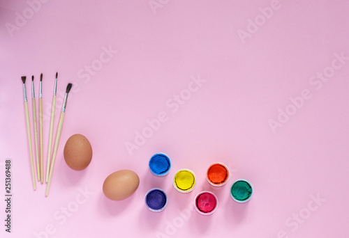 Easter flatlay composition with paintings, brushes and chicken eggs preparing for coloring on pink background with copyspace from top view. Concept of holiday, children, fun.