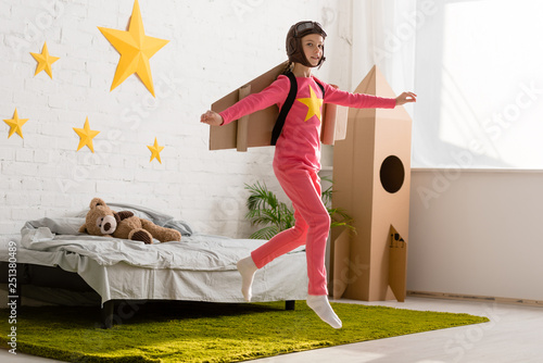 Inspired kid with cardboard wings jumping in bedroom with smile