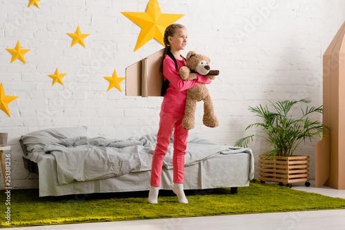 Kid with teddy bear standing on tiptoe and looking away in bedroom