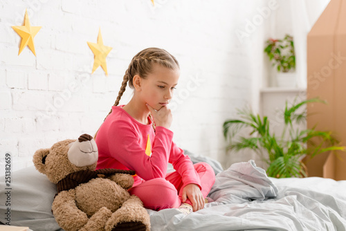 Pensive child with braids sitting on bed with teddy bear