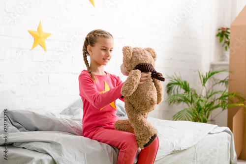 Charming kid with braids sitting on bed and looking at teddy bear