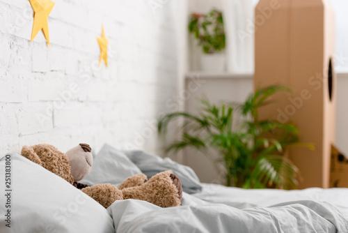 Brown teddy bear lying on bed in bedroom