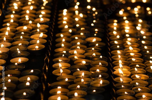 Many beautiful lit candles in a row glowing with a golden yellow light - selective focus © Michele Ursi