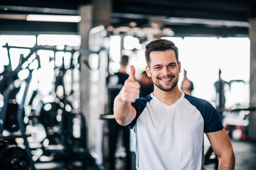 Athlete showing thumbs up in the gym, looking at camera.