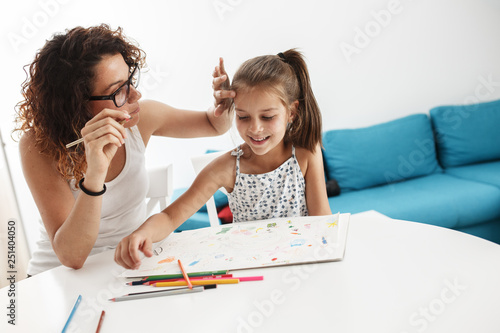 Mother teach her daughter to draw.They sitting at the table in living room. © SolisImages