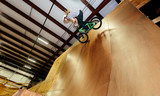 Man jumping and riding on a BMX bicycle at an extreme sports park
