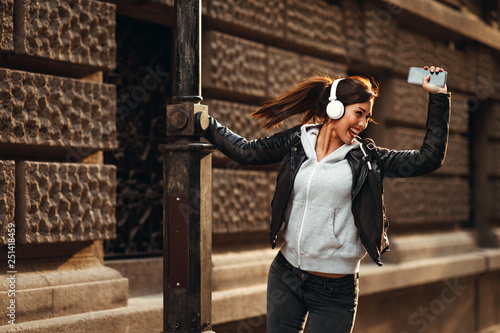 Young woman enjoys music on the street and dancing © djile
