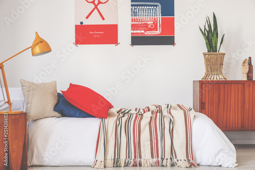 Real photo of a red and blue bedroom interior with a bed, lamp and posters