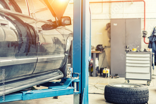 Car service center. Old rusty offroad SUV vehicle raised on lift at maintenance station. Automobile repair and check up - 251452050