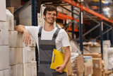 Cheerful worker wearing uniform and white t shirt, holding yellow clipboard. Handsome man smiling, standing and leaning on white boxes in warehouse. Concept of entrepot and commercial industry.