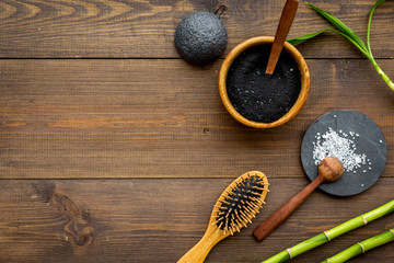 Skin cleansing and detox. Bamboo charcoal powder cosmetics on dark wooden background top view copy space © 9dreamstudio