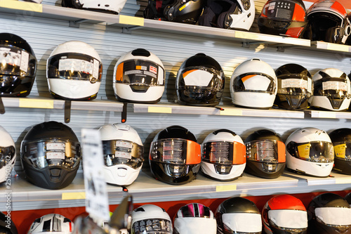 Interior of moto salon with colorful motorcycle helmets on shelves