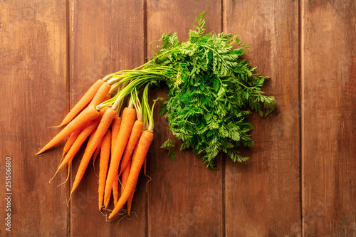 An overhead photo of fresh organic raw carrots on a dark rustic wooden background with copy space - 251506680